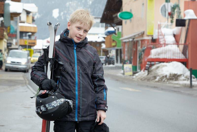 Jongen in skikostuum met ski en helm in handen royalty-vrije stock afbeelding
