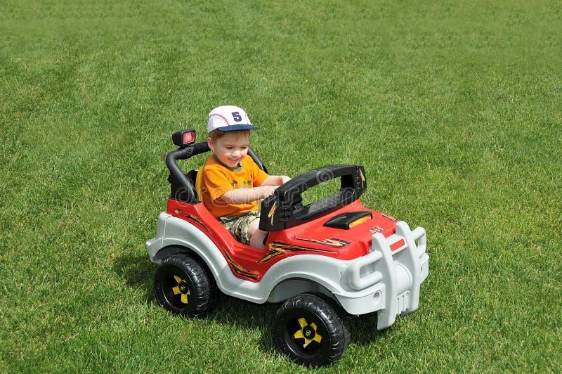 Jongen in stuk speelgoed auto op gras stock foto
