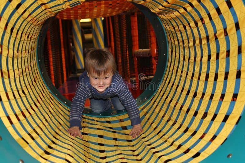 Jongen in tunnel op speelplaats stock afbeeldingen