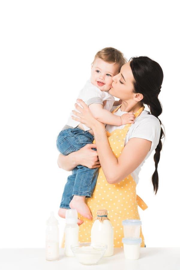jongen van de moeder de kussende baby in wang bij lijst met kinderenvoedsel royalty-vrije stock afbeelding