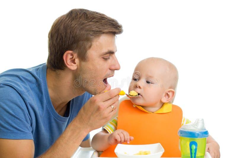 Jongen van de vader de voedende baby stock foto's