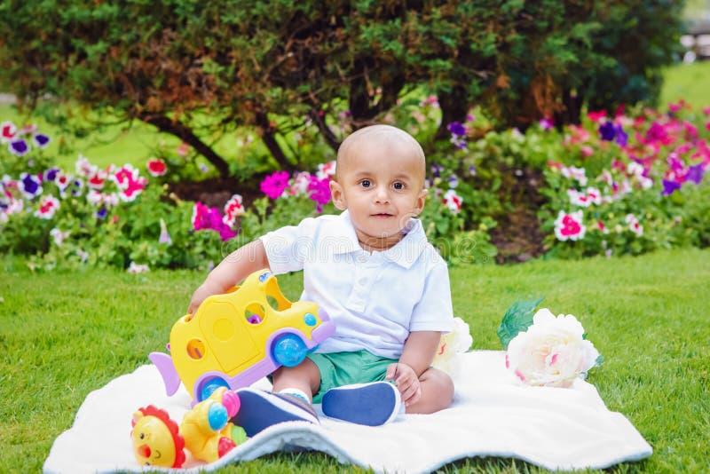 Jongen van de zuiden de Aziatische Indische baby in park op grond stock foto