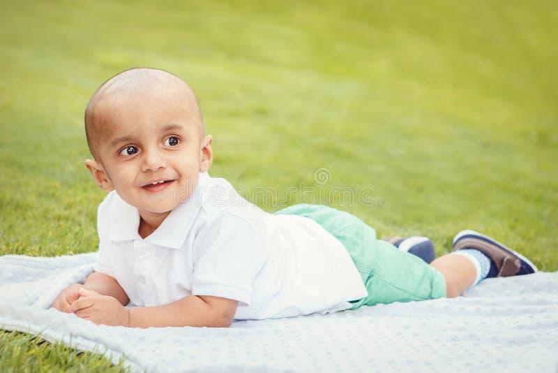 Jongen van de zuiden de Aziatische Indische baby in park op grond royalty-vrije stock foto's