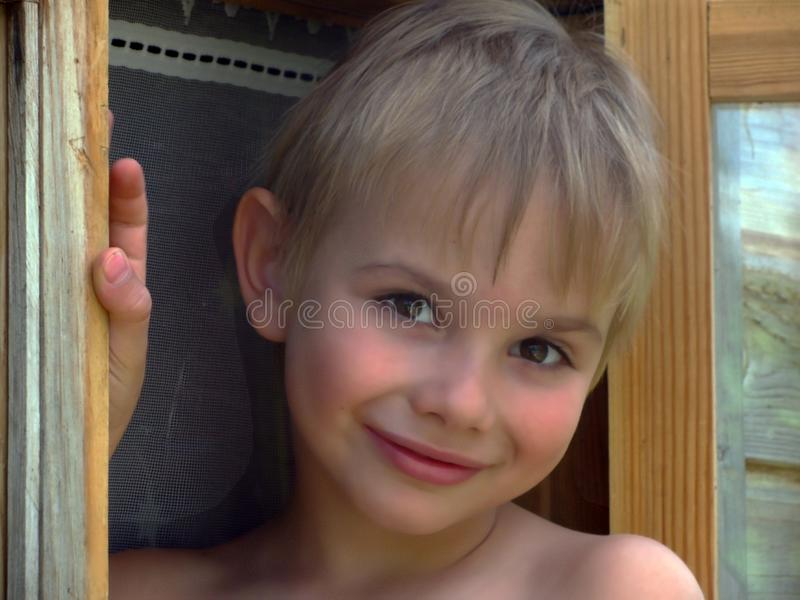 Jongen in venster stock fotografie