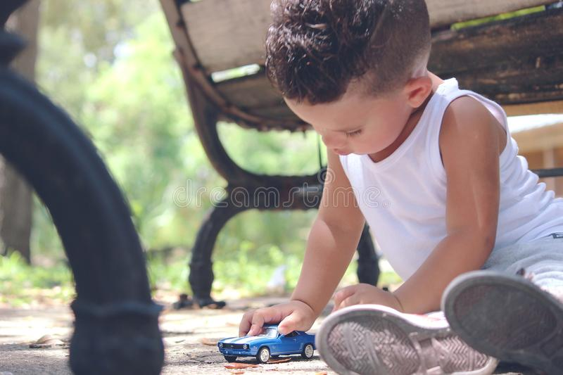 Jongen in White Tank Top Spelling Blue Coupe Die Cast Near Brown Wooden Bench-stoel overdag stock fotografie
