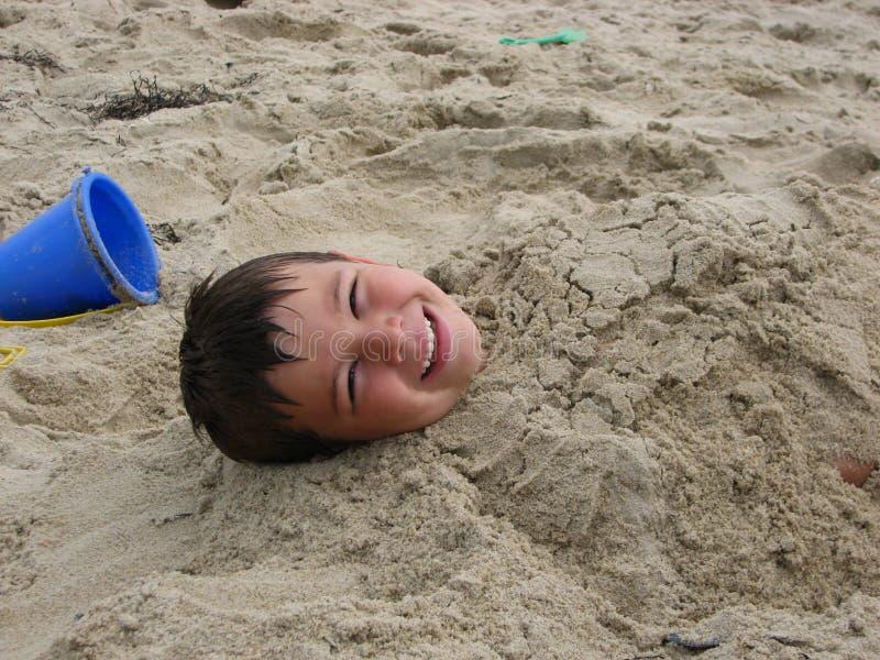 Jongen in zand stock foto