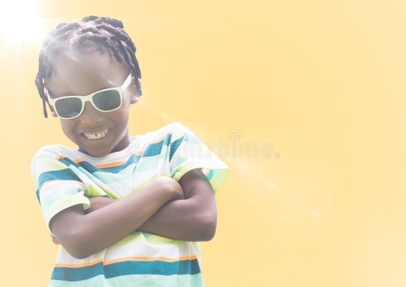 Jongen in zonnebrilwapens tegen gele achtergrond met gloed worden gevouwen die royalty-vrije stock fotografie