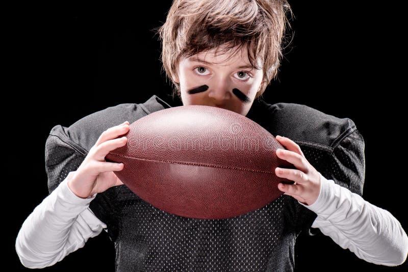 Jongens Amerikaanse voetbalster in beschermende het rugbybal van de sportkledingsholding royalty-vrije stock foto