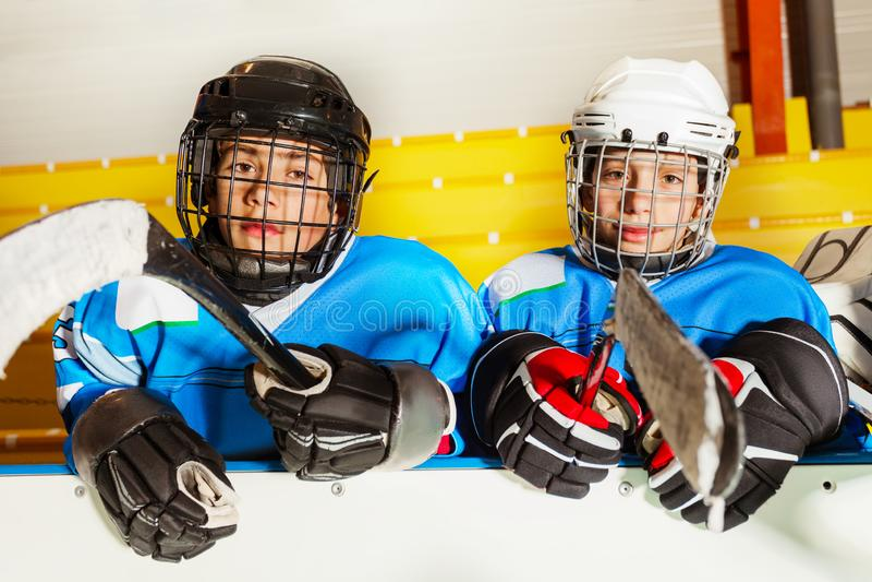 Jongens in beschermingsmiddel bij ijshockeystadion stock afbeeldingen