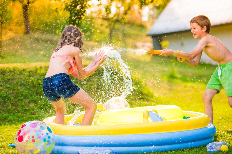 Jongens bespattend meisje met waterkanon, tuin zwembad stock afbeeldingen
