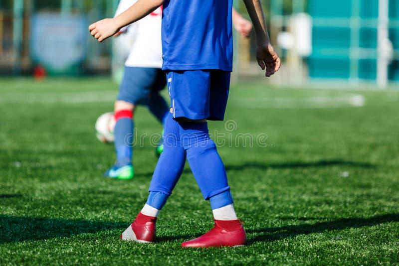 Jongens bij blauwe witte sportkledingslooppas, dribble, aanval op voetbalgebied r Opleiding stock fotografie
