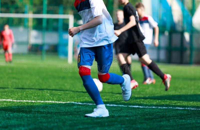 Jongens bij blauwe witte sportkledingslooppas, dribble, aanval op voetbalgebied r Opleiding royalty-vrije stock afbeelding