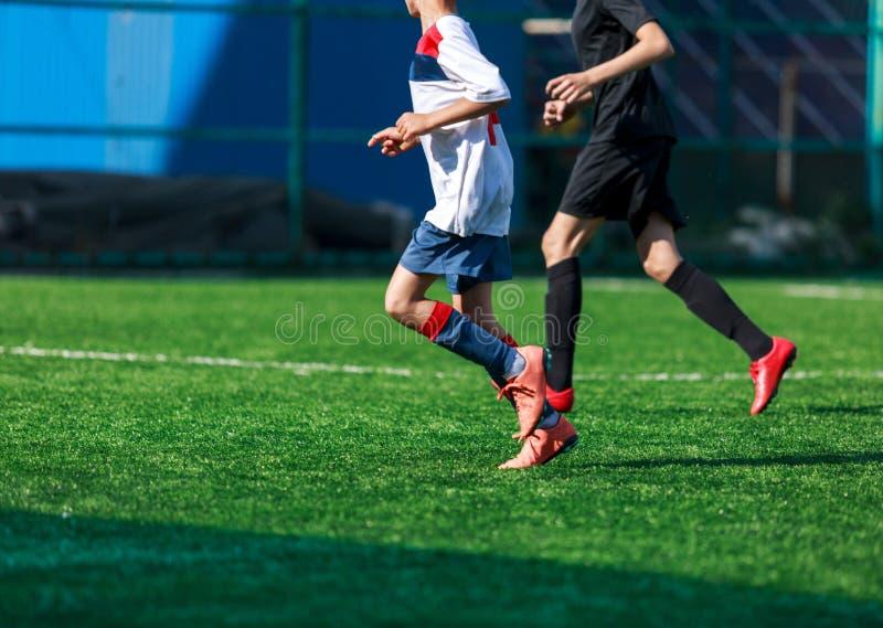 Jongens bij blauwe witte sportkledingslooppas, dribble, aanval op voetbalgebied r Opleiding stock afbeeldingen