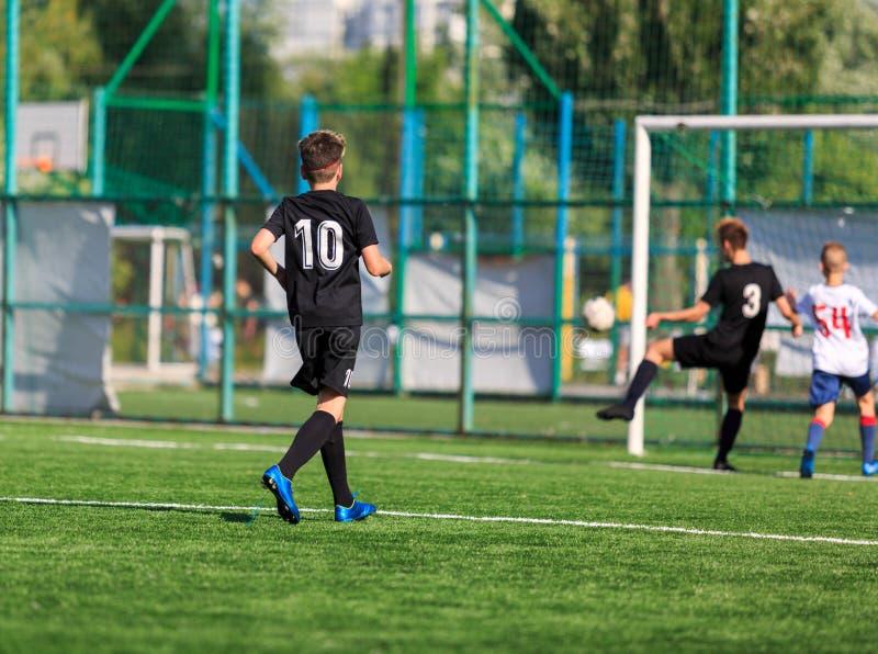 Jongens bij blauwe witte sportkledingslooppas, dribble, aanval op voetbalgebied r Opleiding stock afbeelding