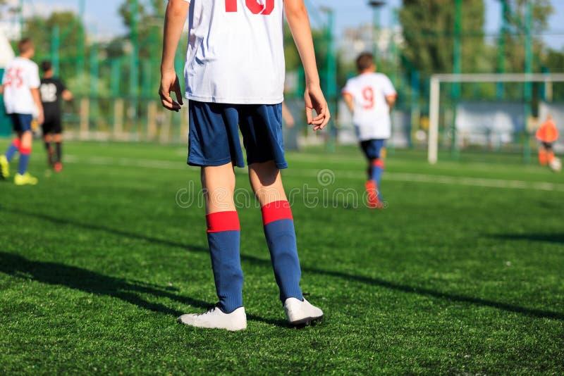 Jongens bij blauwe witte sportkledingslooppas, dribble, aanval op voetbalgebied r Opleiding royalty-vrije stock afbeeldingen