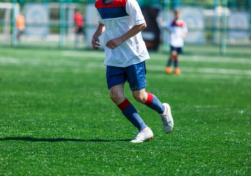 Jongens bij blauwe witte sportkledingslooppas, dribble, aanval op voetbalgebied r Opleiding stock foto's