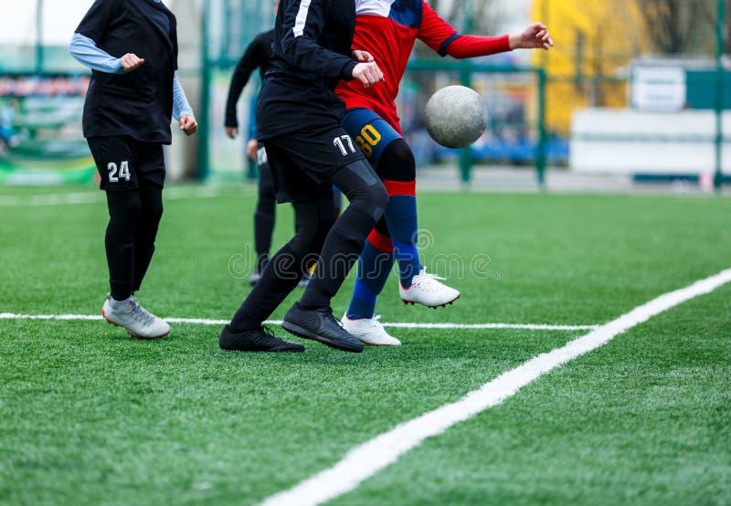 Jongens bij zwarte rode sportkledingslooppas, dribble, aanval op voetbalgebied r Opleiding stock afbeelding