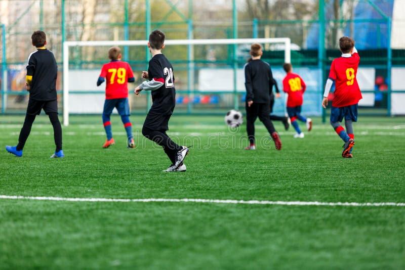 Jongens bij zwarte rode sportkledingslooppas, dribble, aanval op voetbalgebied r Opleiding royalty-vrije stock afbeelding