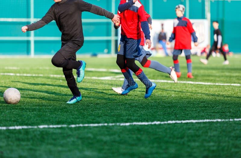 Jongens bij zwarte rode sportkledingslooppas, dribble, aanval op voetbalgebied r Opleiding stock foto