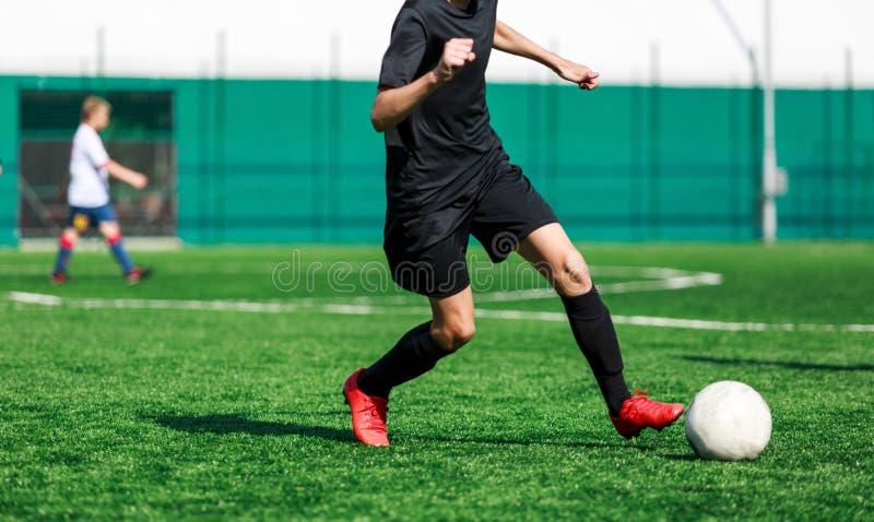 Jongens bij zwarte sportkledingslooppas, dribble, aanval op voetbalgebied r Opleiding royalty-vrije stock afbeelding