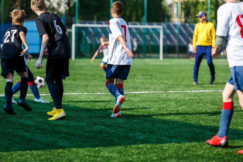 Jongens bij zwarte witte sportkledingslooppas, dribble, aanval op voetbalgebied r Opleiding royalty-vrije stock afbeelding