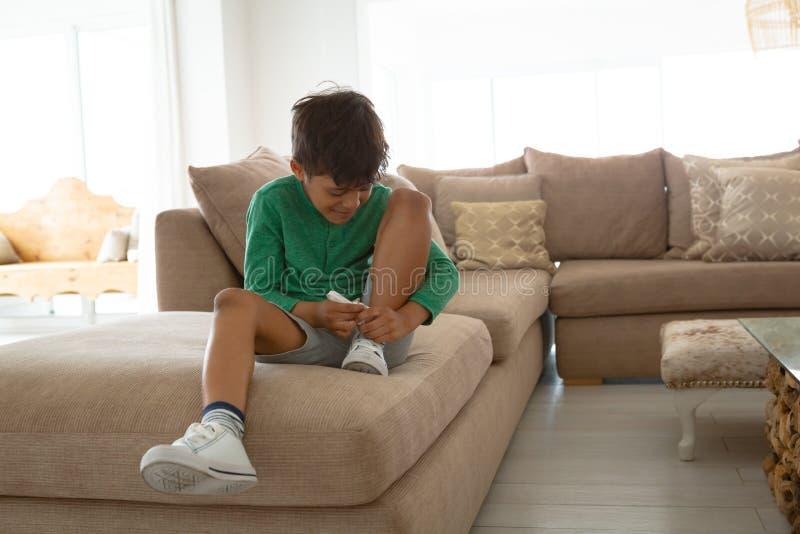Jongens bindende schoenveter op bank in woonkamer bij comfortabel huis royalty-vrije stock foto's