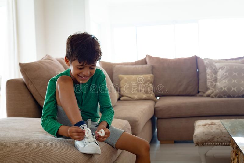 Jongens bindende schoenveter op bank in woonkamer bij comfortabel huis stock afbeelding