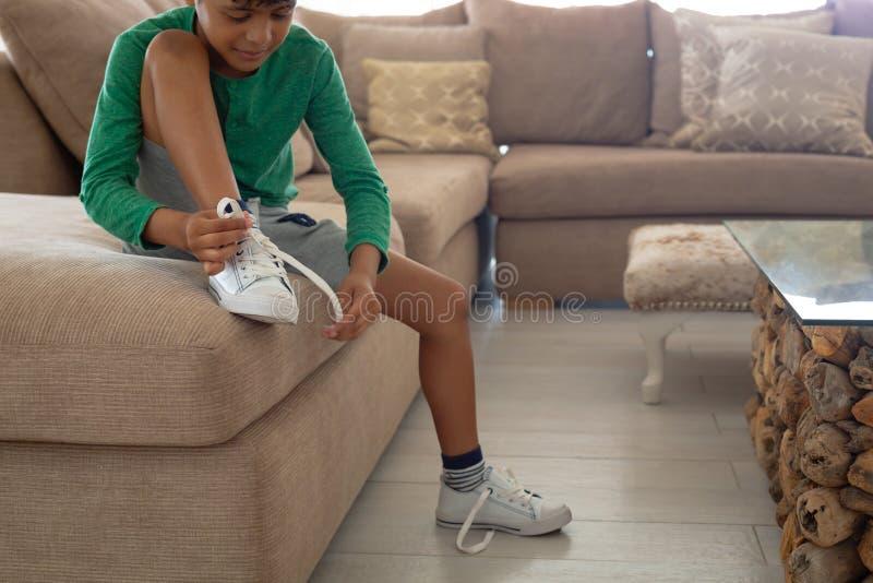 Jongens bindende schoenveter op bank in woonkamer bij comfortabel huis royalty-vrije stock afbeelding
