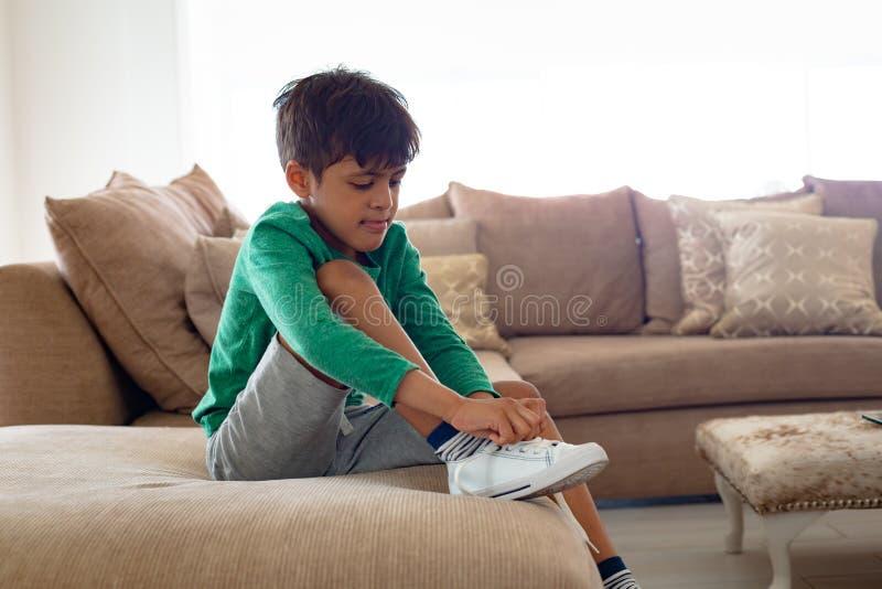 Jongens bindende schoenveter op bank in woonkamer bij comfortabel huis royalty-vrije stock afbeeldingen