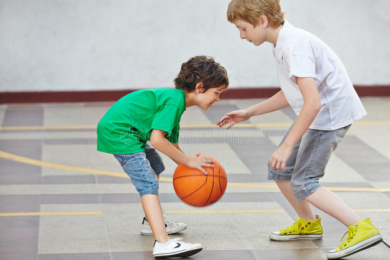 Jongens die basketbal in school spelen stock afbeelding