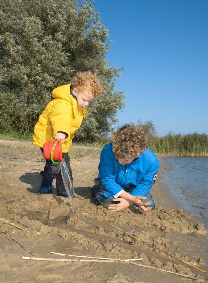 Jongens die bij Strand spelen stock fotografie