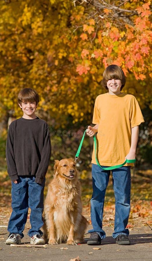 Jongens die de hond lopen stock afbeeldingen