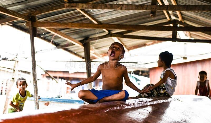 Jongens die in een boot spelen stock foto's