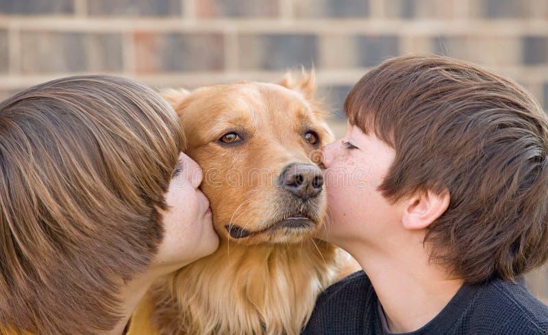 Jongens die een Hond kussen stock afbeeldingen