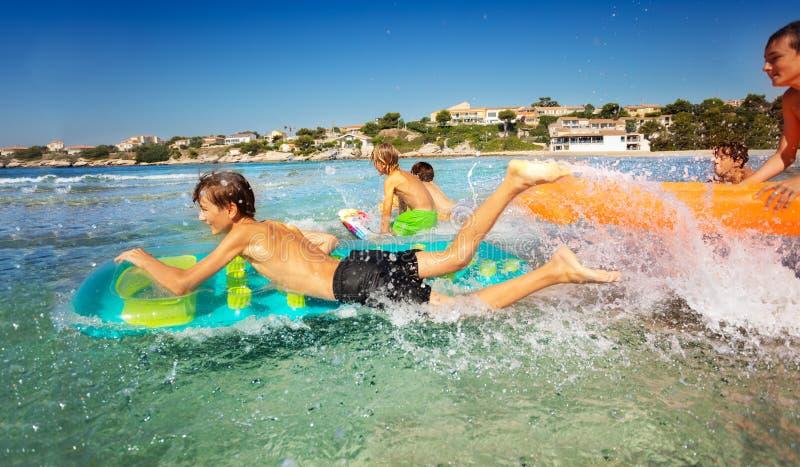 Jongens die pret bespattend water hebben terwijl het overzeese zwemmen royalty-vrije stock fotografie