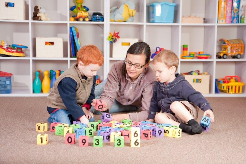 Jongens die spel met jonge geitjesblokken spelen met moeder stock afbeeldingen