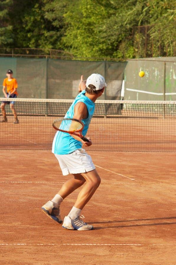Jongens die tennis spelen stock fotografie
