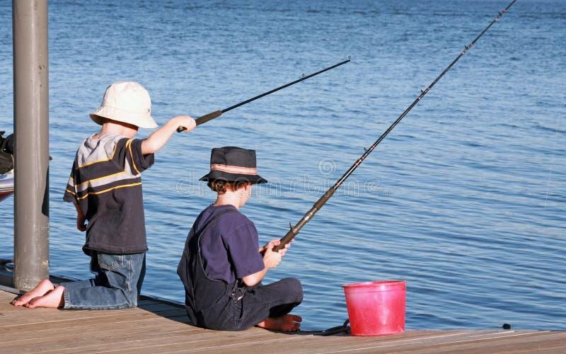 Jongens die van Pijler vissen stock foto's