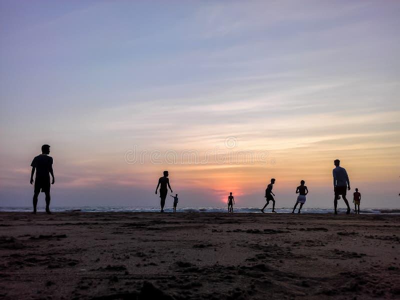 Jongens die voetbal op het strand, mooie zonsondergang op achtergrond spelen royalty-vrije stock afbeelding