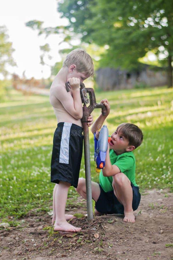 Jongens die watergom vanaf droog werken goed te vullen stock afbeelding