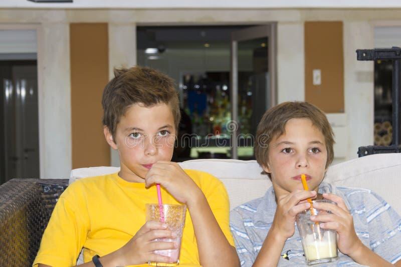 Jongens met glazen van milkshake stock afbeeldingen