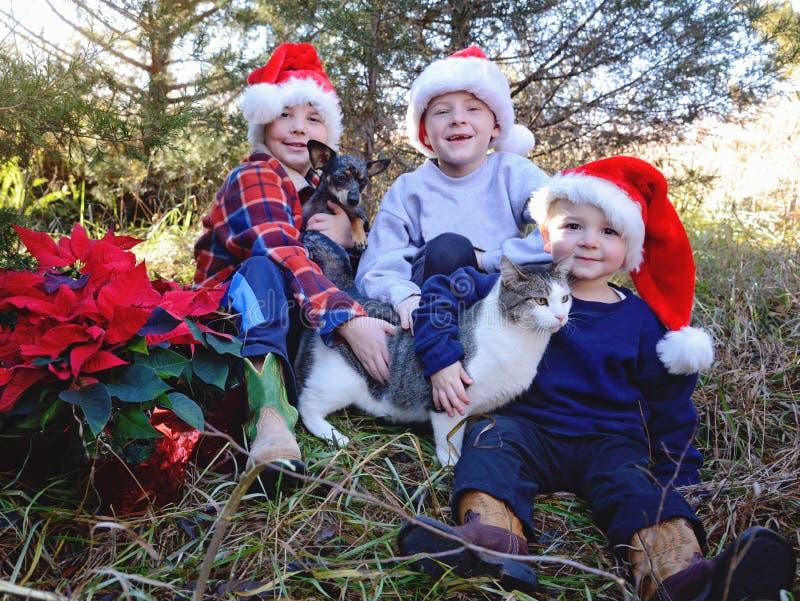 Jongens met kerstmantel stock foto's
