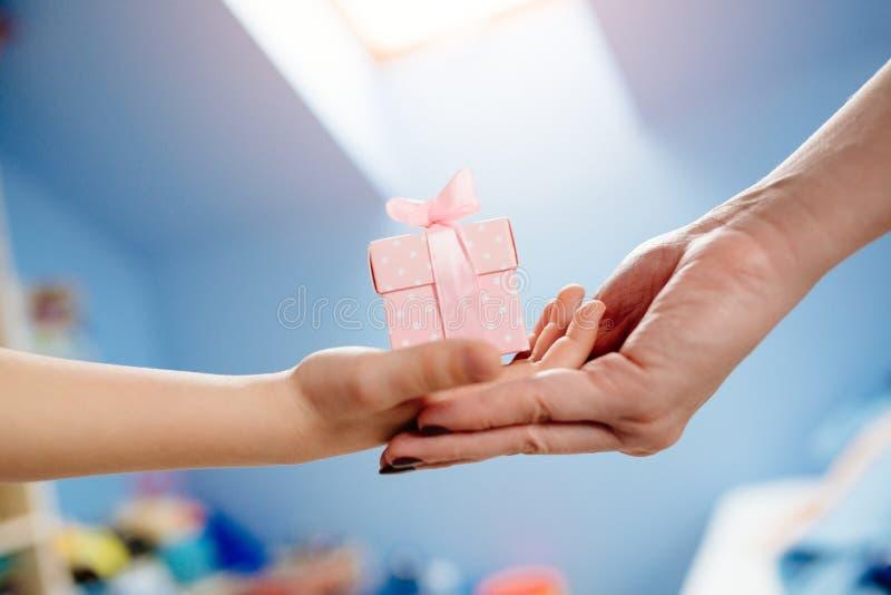 Jongens` s handen die een gift geven aan zijn moeder - Moeder` s Dag royalty-vrije stock afbeeldingen