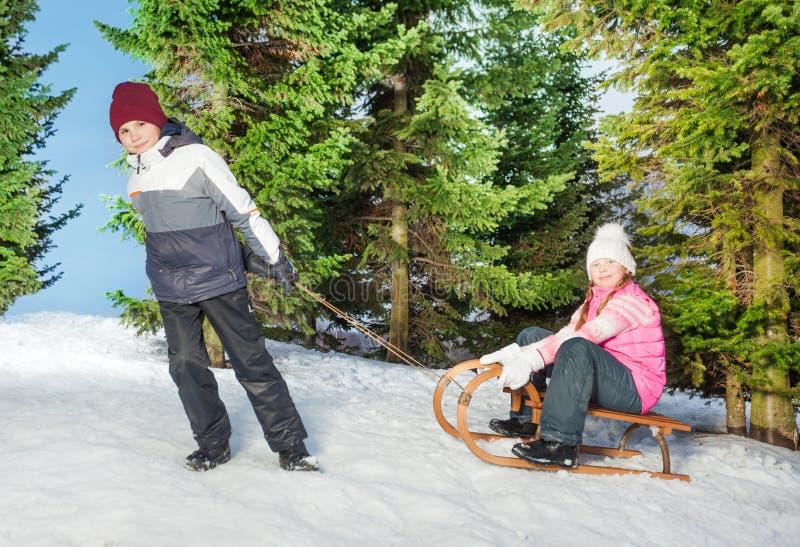 Jongens sledging meisje aan een heuvel in het de winterbos royalty-vrije stock afbeelding