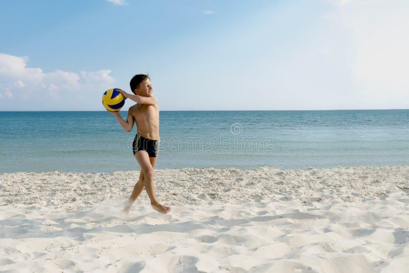 Jongens speel en lopende bal van valleyball bij het overzeese strand stock foto's