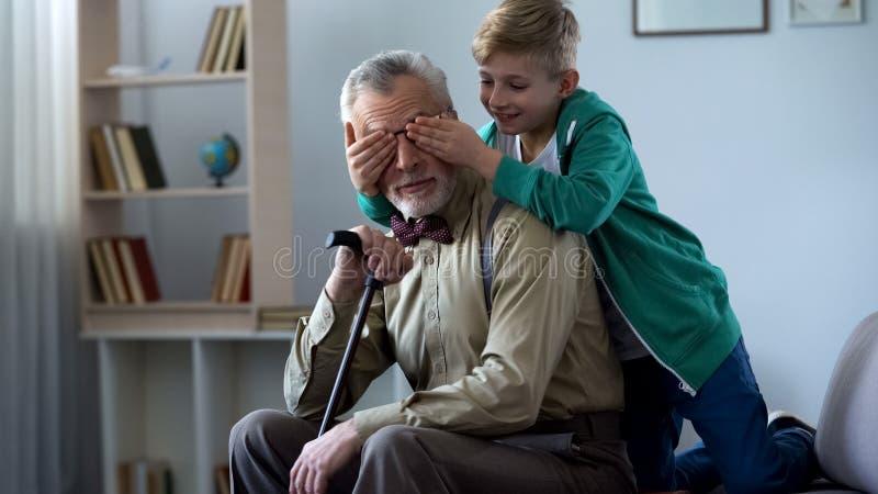 Jongens speel en sluitende grootvader samen in het weekend ogen, die pret hebben royalty-vrije stock afbeeldingen