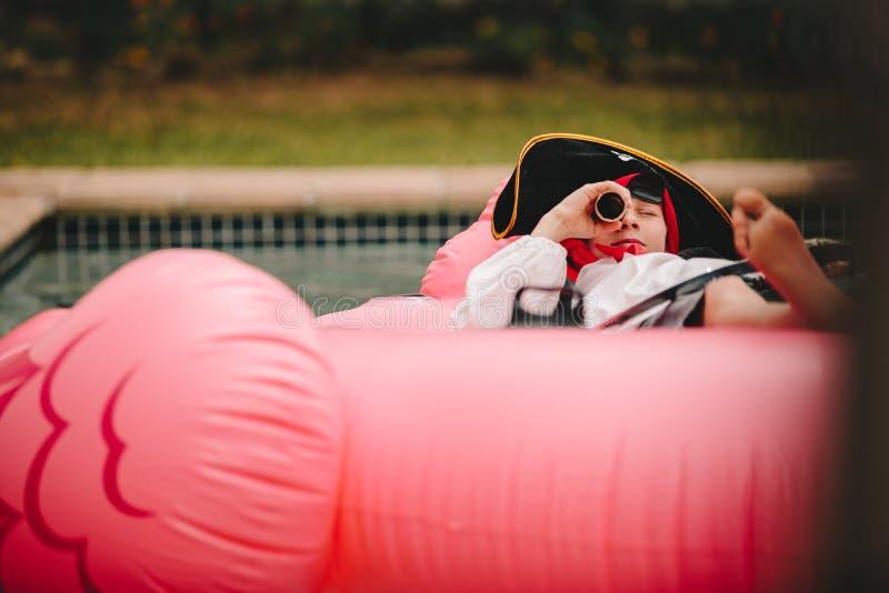 Jongens speelpiraat in pool stock foto