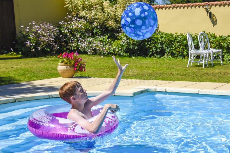Jongens speelvangst in zwembad stock foto's
