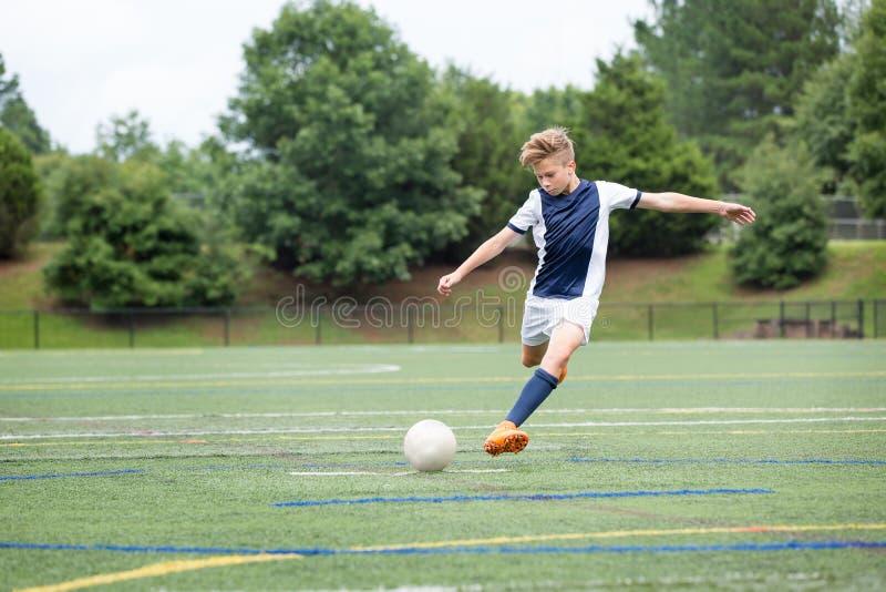 Jongens Speelvoetbal die - de bal schoppen stock fotografie
