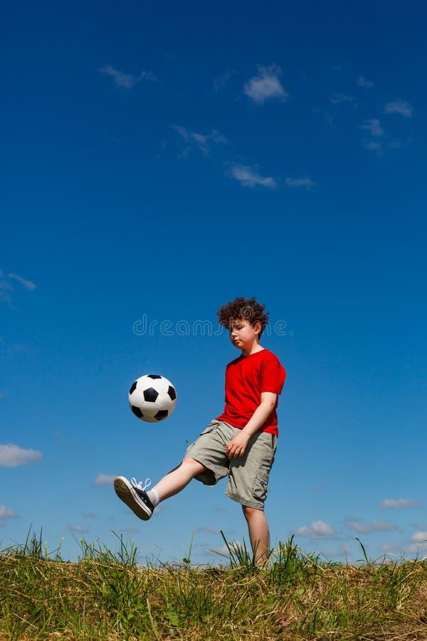 Jongens speelvoetbal openlucht royalty-vrije stock afbeeldingen